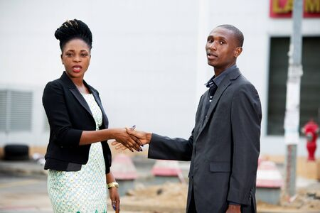 Handshake between a man and a businesswoman meeting in the street
