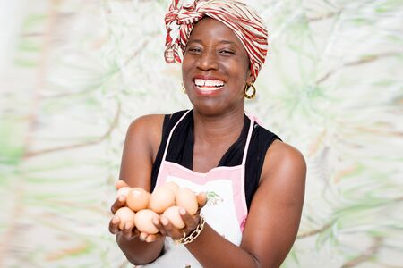 young happy woman standing in a studio with green background, holding organic eggs in hands Stock Photo