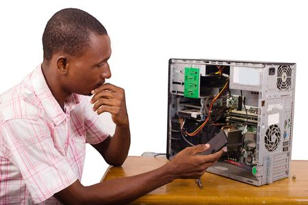 young technician sitting thinking with a desktop computer in front of him and holding a mobile phone. Standard-Bild