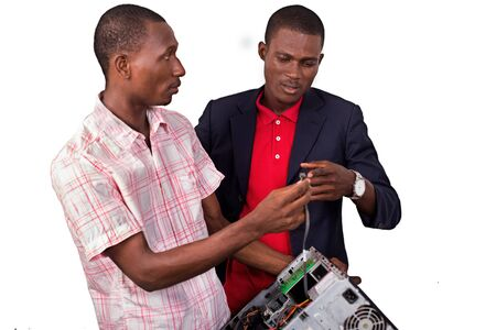 Technician repairing a computer in an office in front of his boss