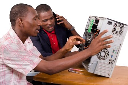 two technicians sitting at the desk working together on a computer
