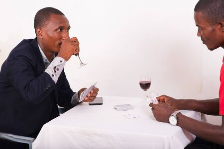 positive man holding a pack of cards playing card games with his friend and drinking wine