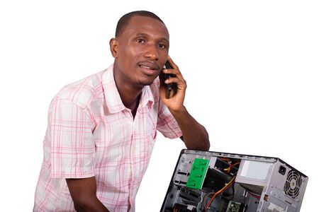 Young technician leaning against a broken computer and speaking on the phone