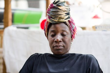 portrait of African woman sitting in a chair and sleepy behind her sales display
