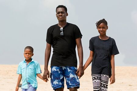 a young man with his children at the beach walking back to the sea hands in hands.