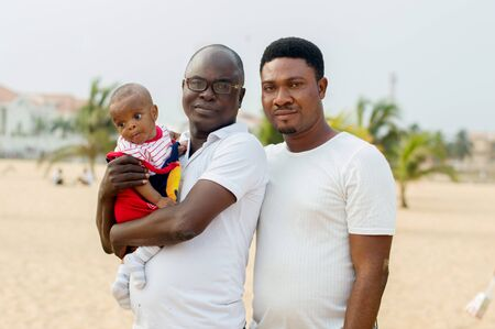 a young man in glasses and dressed in white shirt standing with his friend at the beach holding his baby sticking to his chest and look at the camera.