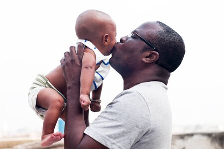 Adult man giving a kiss to his baby raised in his arms.