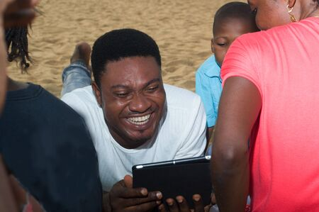 a man lying on the sand with a tablet in his hand and looking at something with his family smiling.