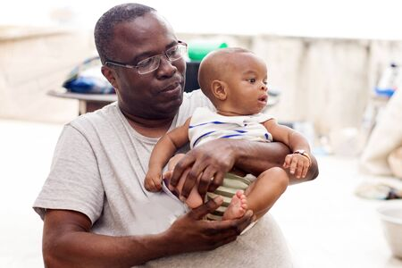 a young man in glasses and gray t-shirt admiring his baby with a smile.