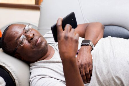 Mature man lying on the couch and reading messages on his cell phone.