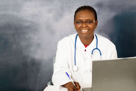 young female doctor sitting at the desk in front of a laptop,look at the camera and write a medical prescription