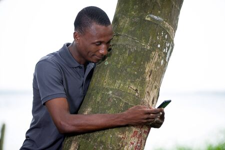 young man leaning against a coconut tree looking on the screen of his mobile phone Stok Fotoğraf