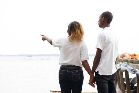 couple standing back on a dock holding hands and watching the horizon show by the woman Stockfoto