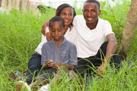 Retrato de familias sonrientes sentados en el parque relajándose y disfrutando de la naturaleza