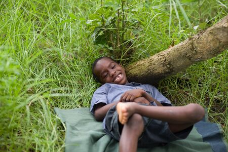 Happy little child lying on the grass dreaming and smiling. Imagens