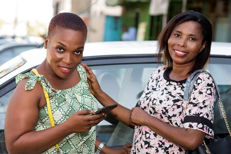 two young women standing near a car talking with a smile. Zdjęcie Seryjne
