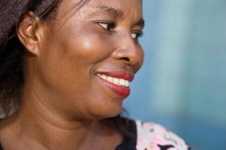 Gros plan d'un beau visage de femme souriante et confiante sur fond bleu