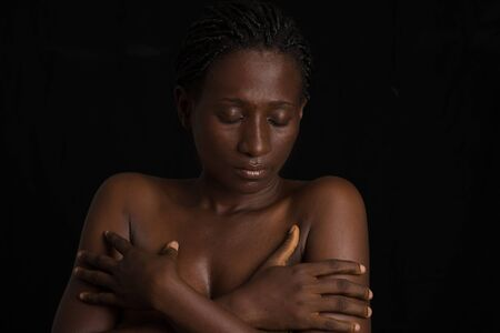 portrait of woman with beautiful skin posing naked torso and hands on breast isolated black background