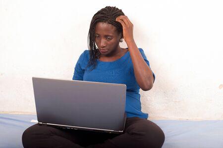 portret van een vrouw die aan een laptop werkt die op haar dijen ligt en in haar haar krabt.