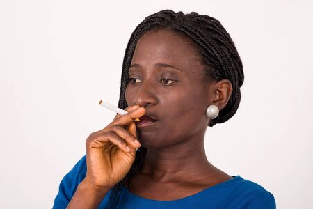 young girl standing on a white background and blue cigarette in her mouth, look at the camera.. Stock fotó