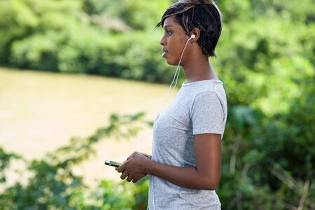 Young sporty woman listens music on mobile phone after workout at park Banco de Imagens