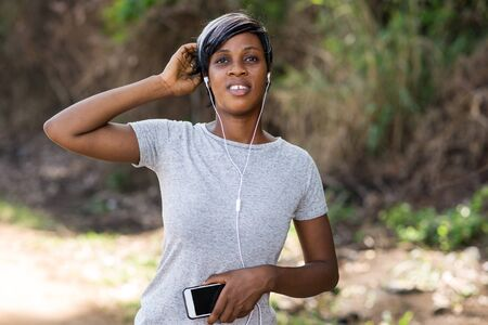 Woman listening to music on her mobile phone during outdoor workout having rest and hand on head Banque d'images