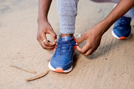 young sporty woman trying to tie her laces.