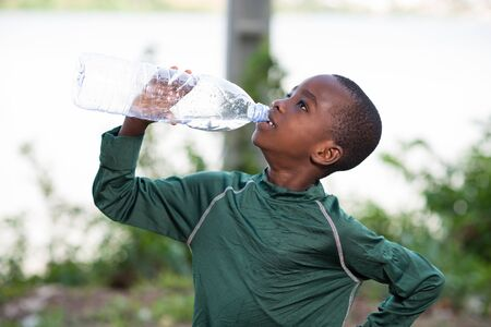 Young boy drinking fresh water from plastic bottle after sport in the outdoors.
