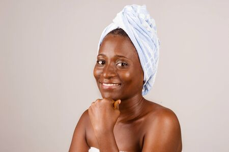 African girl sitting on gray background, bath towel knotted on the head smiling with the hand under the chin. 免版税图像