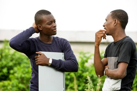 two young student chatting and laughing standing outdoors with a computer in their hands