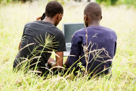 two young students talk, work in front of a laptop and relax while sitting back to the camera in the park.