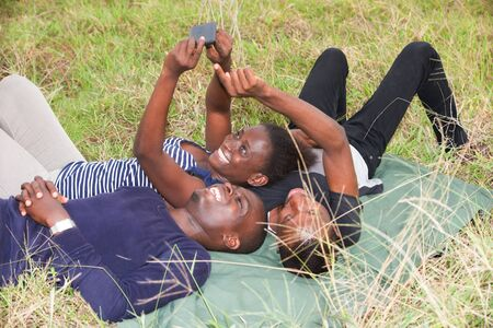 Happy group of young friends lying on the grass outdoors and looking at a cell phone