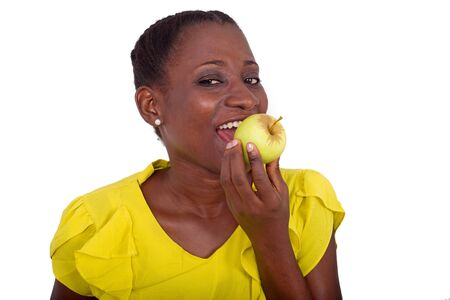 young girl standing in yellow camisole holding an apple on her mouth and looking at camera smiling.