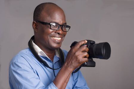 African man standing in blue shirt on gray background looking ahead with camera in hand. 版權商用圖片