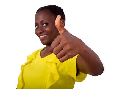 young girl standing in yellow camisole making thumb sign smiling on camera. Stock Photo