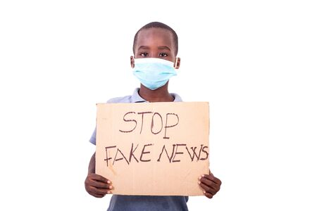 little boy wearing a medical mask, holding a paper with STOP FAKE NEWS text.