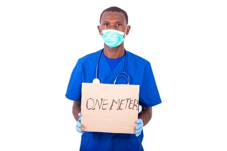young serious doctor, wearing uniform with medical mask holding a paper with a text ONE METER.
