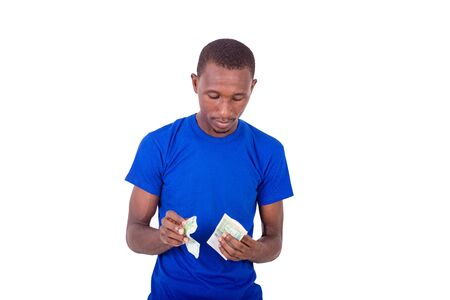 a young man in a blue t-shirt standing on a white background looking at banknotes. 스톡 콘텐츠