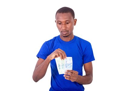 a young man in a blue t-shirt standing on a white background holding banknotes while thinking.
