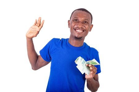 a young man in a blue t-shirt standing on a white background with banknotes gesturing with his hand and smiling at the camera.