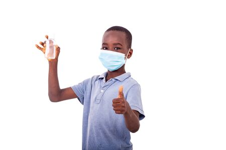 a little boy with a medical mask holding an antibacterial gel while showing his thumb.