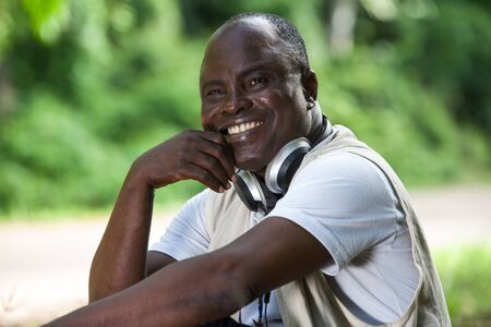 Close-up portrait of a man smiling and expressing happiness sitting in a park, enjoying the weather and listening to music.