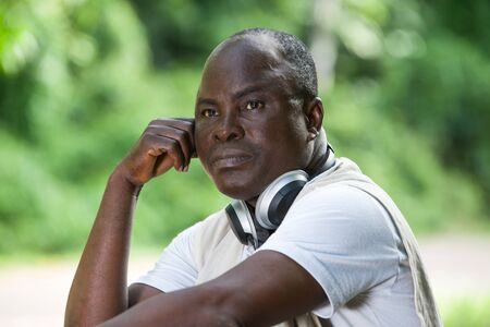 mature man sitting in dreamy and thoughtful forest sitting with a music headset at his neck