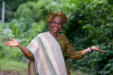 jeune femme africaine debout tenue traditionnelle et lunettes souriantes mains tendues.