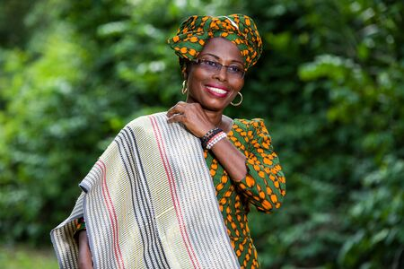 young african woman standing traditional dress and glasses well placing his escapes smiling.
