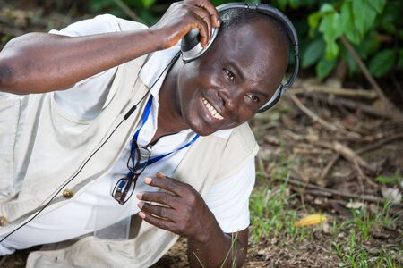 Laughing mature man lying on green grass with headphones, listens to music Banque d'images