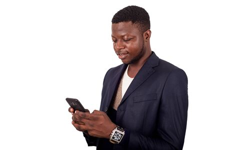 Great news! Handsome young man using his phone with smile while standing against white background. Stock fotó