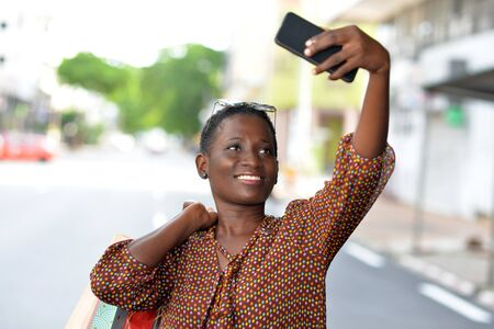 woman gets photos with a smart phone after a shopping in the city