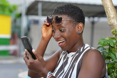 cheerful young woman sitting outside, holding her sunglasses up and looking on screen of a smart phone in hands laughing