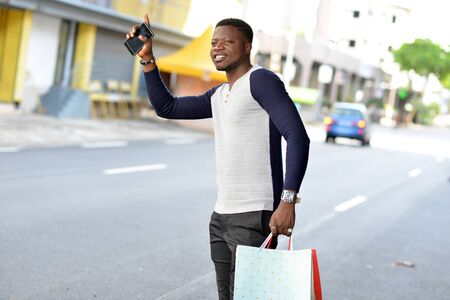 young african man standing in polo on the street after shopping and looking in front of him smiling.